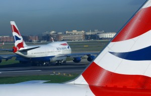 British Airways plane takes off, while another British Airways plane taxis by in foreground.