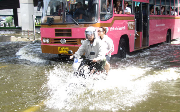 Thailand floods, couple on motor bike travel on flooded streets