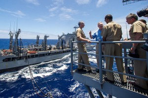 Secretary of the Navy Ray Mabus (blue shirt) observes an at sea biofuel replenishment by the Great Green Fleet