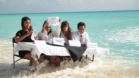 Young people sit around a wave-submerged negotiating table at the 2010 UN climate talks (Pic: Bunkerfilms.com / 350.org)