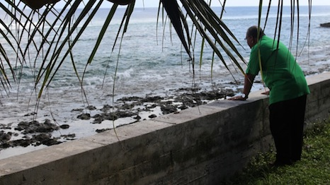 Loeak stands by a sea wall he built himself to stop the rising oceans flooding his land
