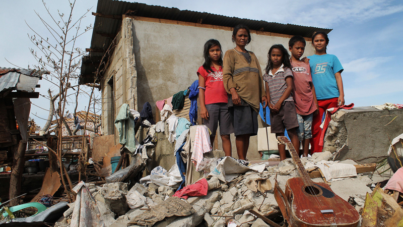 Corazon dela Cruz and her four children in the wreckage of their home destroyed by Typhoon Haiyan (Pic: Pio Arce/Genesis Photos - World Vision)