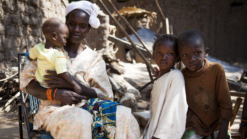 Awa sits with her son Modiba and his siblings at their home in Mali. Modiba is suffering from severe malnutrition and malaria. (Pic: Dave The Children/Flickr)