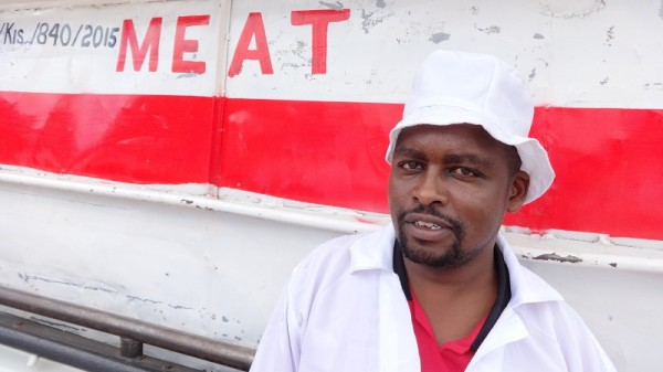 Isaac Nemuta next to a meat transport van in the slaughterhouse