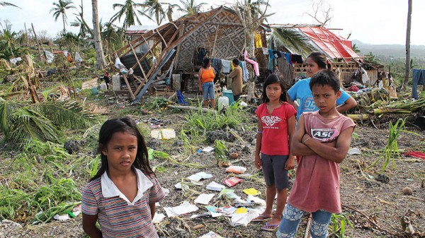 Children and the remains of their school after Typhoon Haiyan hit the Philippines in 2013 (Pic: EU Commission/Flickr)