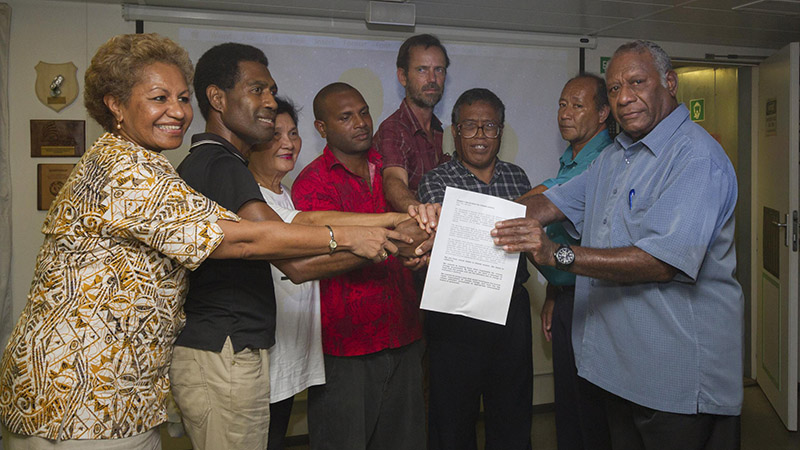 Vanuatu president Baldwin Lonsdale (far right) holds the declaration on climate justice with fellow delegates (Pic: Steven Lyon / Greenpeace)