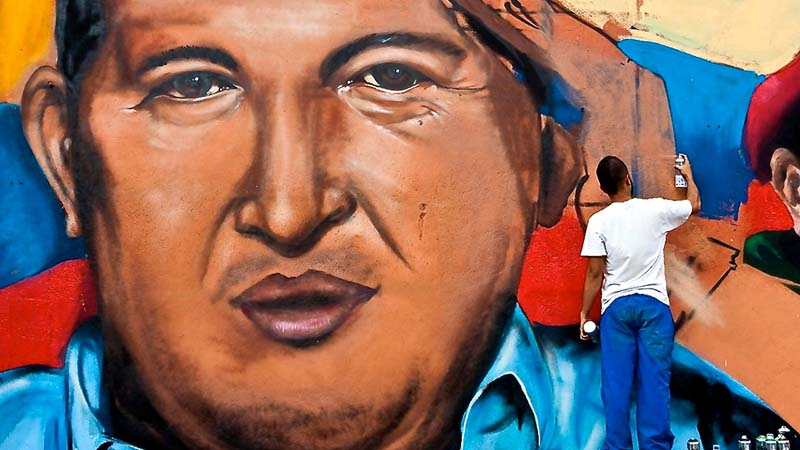 A man paints a mural of late leader Hugo Chavez who died in 2013 (Flickr / Antonio Marin Segovia)