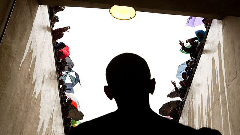 Silhouette of President Obama as he is cheered bby South African fans before speaking at Nelson Mandela's memorial in 2013 (Flickr/ White House, Pete Souza)