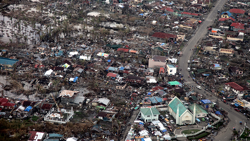 erial view of Tacloban after Typhoon Haiyan A church on the outskirts of Tacloban is one of the few buildings to remain unscathed after Typhoon Haiyan devastated the city on 8 November 2013. Two and a half weeks on from the disaster the main roads have been cleared and aid is getting through but, many people remain in need of assistance. The UK is providing £55m in humanitarian aid, in the form of shelter kits, food, medicine and water purification tablets, as well as Royal Navy ships and Royal Air Force planes to help distribute the aid to remote areas.