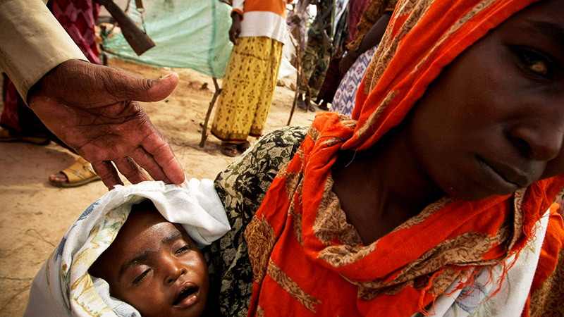 A woman holds her severely malnourished young child in a camp for Internally Displaced Persons (IDPs) in Mogadishu in 2011, during a sever drought that hit the region (Pic: UN photos)
