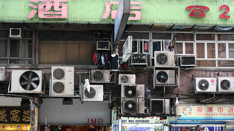 Air conditioning units hang from the side of a building in Hong Kong. Their growing use is growing 10-15% a year, intensifying global warming (Flickr/ Niall Kennedy)