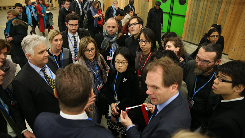 During the final days of the negotiations, delegates huddle in the corridors before receiving the revised draft Paris outcome