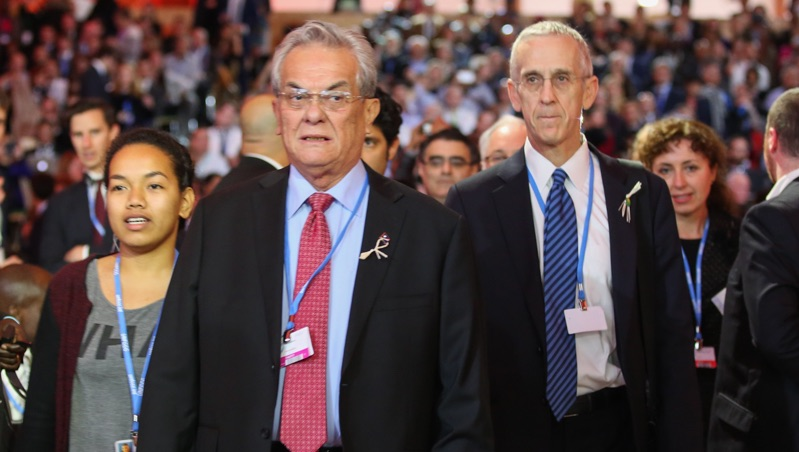 Marshall Islands minister Tony de Brum walks into the final session of talks with US envoy Todd Stern, both wearing a coconut leaf (Photo by IISD/ENB | Kiara Worth)