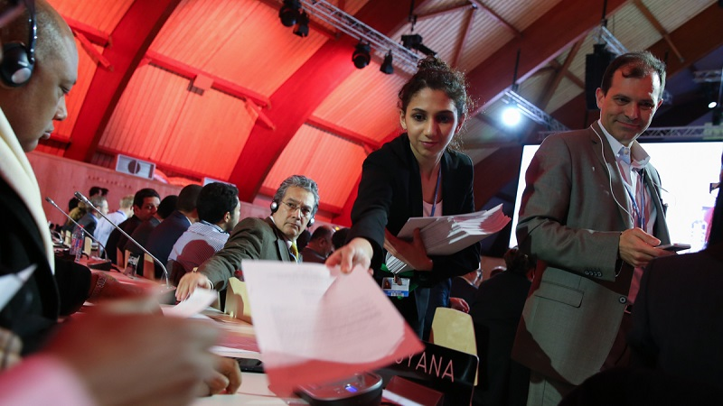 Draft Paris climate agreement being distributed (Photo by IISD/ENB)