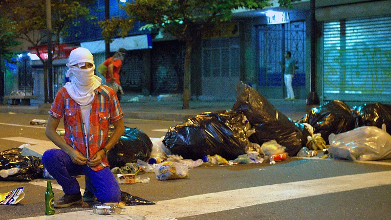 A protester blocking the streets with rubbish in Venezuela, January 2015 (Flickr/Carlos Díaz)