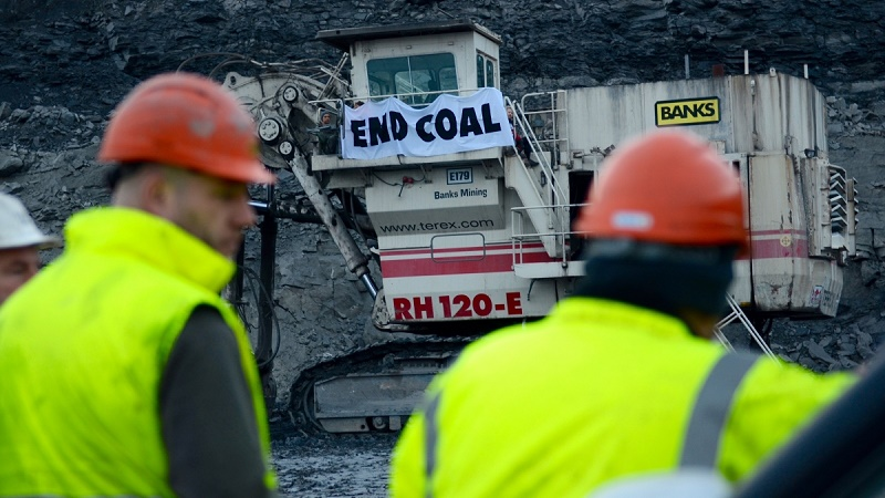 Protesters raised a banner on equipment at Shotton opencast coal mine, UK (Pic: End Coal Now)