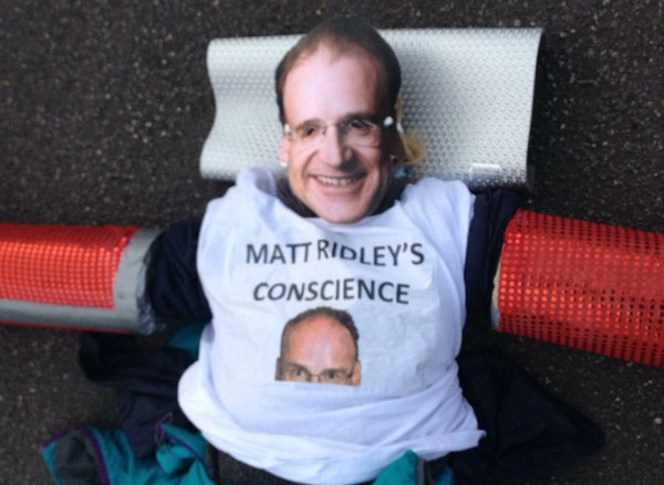 A protestor blocks the mining road, wearing a Matt Ridley mask (Pic: End Coal Now)