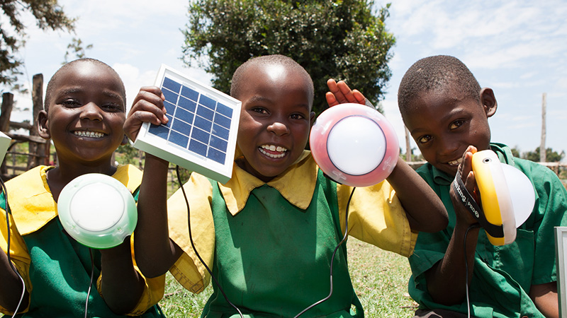 School children from Kembu primary school holding solar lights, Longisa, Bomet county, Kenya (Pic: SolarAid/Flickr)