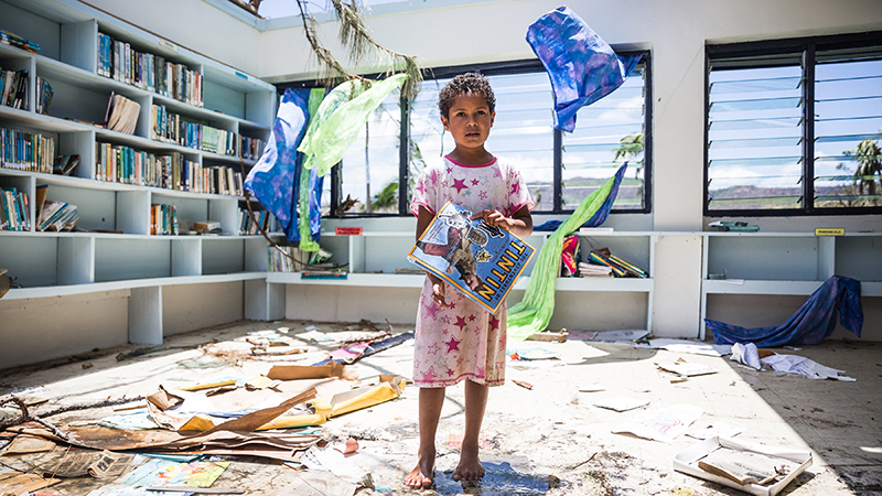 Makelesi, 7, standing in destoryed library of Nabau District School in Ra Province, Fiji. The photo is picture perfect in a very odd way with– bright blue skies and very sunny, however, Mother Nature is a force not to be reckoned with – it only took Cyclone Winston literally minutes to rip off the roof of this classroom. Category 5 Tropical Cyclone Winston made landfall in Fiji on Saturday 20 February, continuing its path of destruction into Sunday 21 February. A state of natural disaster and a nationwide curfew had been declared by the Government of Fiji earlier in the evening. In the wake of Cyclone Winston, UNICEF's main concern is for children, pregnant women and breastfeeding mothers across Fiji. Little is yet known about the status of communities living on the outer islands of Fiji that were directly under the eye of Tropical Cyclone Winston- as communications remain down for many. The Fijian Government is rapidly working to assess the overall situation in order to pinpoint the critical needs. The Fijian Government has declared a state of natural disaster for the next 30 days and has initiated the clean-up process by clearing the huge amounts of debris scattered everywhere. UNICEF staff members are standing by to assist as required.