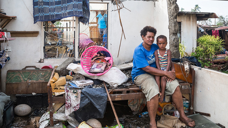 Kalisi holds her son Tuvosa, 3, in the remnants of her house in Rakiraki District in Ra province in Fiji (Pic: UNICEF)