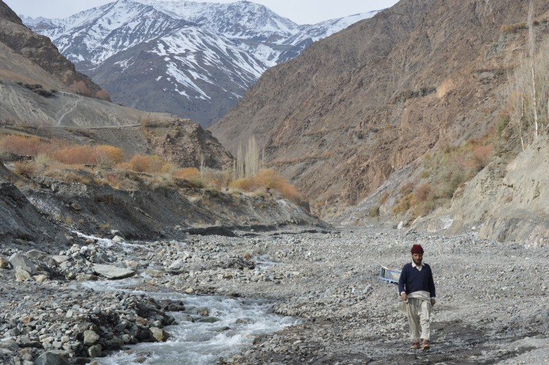 A man walks along a glacial water stream below a snow-covered mountain in Gulkin valley in northern Chitral district of Pakistan Photo: Saleem Shaikh