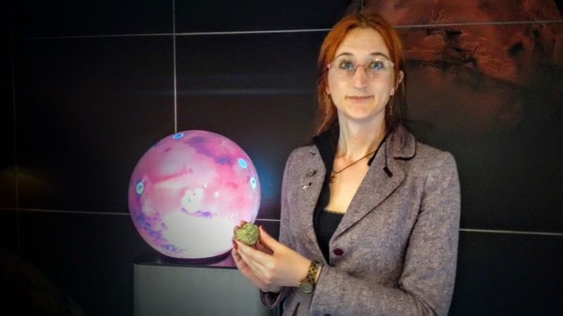 Researcher Adrienne Macartney shows a piece of olivine mineral