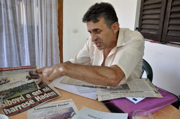 """Ragip Grajcevci is one of the few remaining residents of """"Old Hade"""". The newspaper reads: """"Sibovc puts Hade in limbo"""" (Photo: Karl Mathiesen)"""