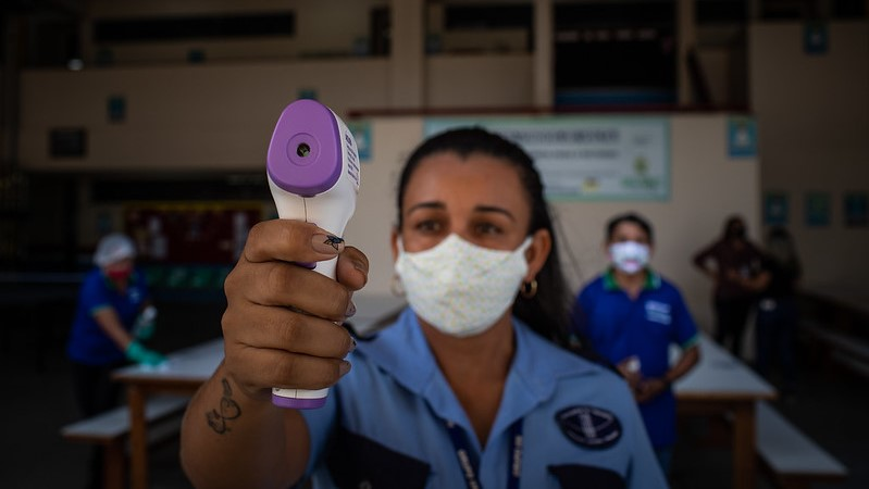 An employee at a school in Manaus, in the state of Amazonas, Brazil, takes the temperature of students arriving for class. (Photo: IMF / Raphael Alves/Flickr)